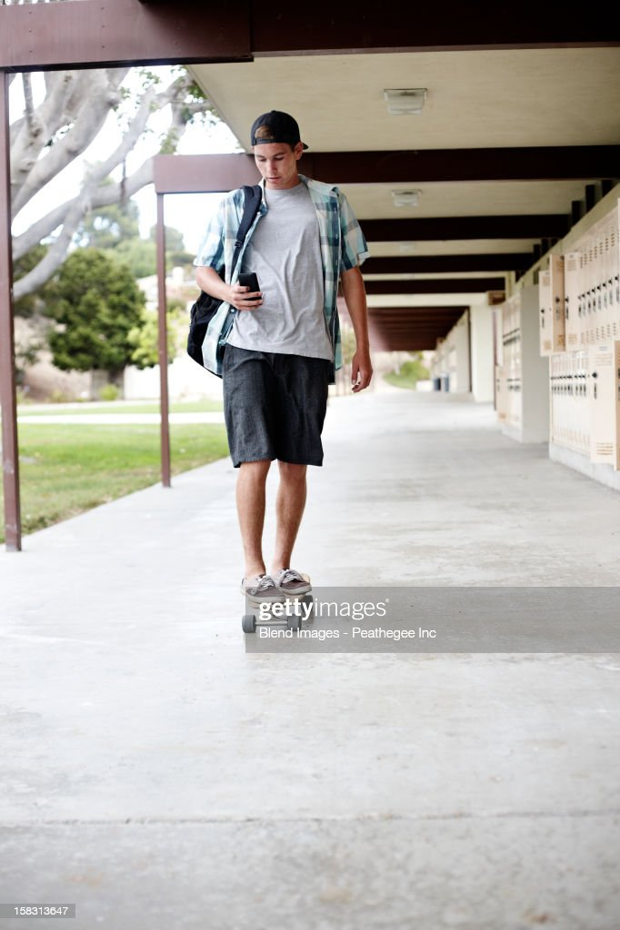Caucasian teenager riding skateboard : Stock Photo