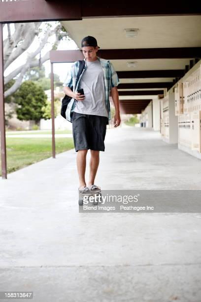 Caucasian teenager riding skateboard