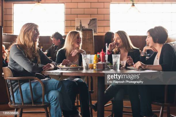 Caucasian teenagers eating together in restaurant