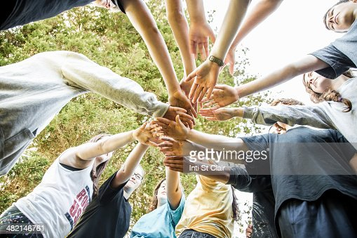 Caucasian teenagers putting hands together in huddle