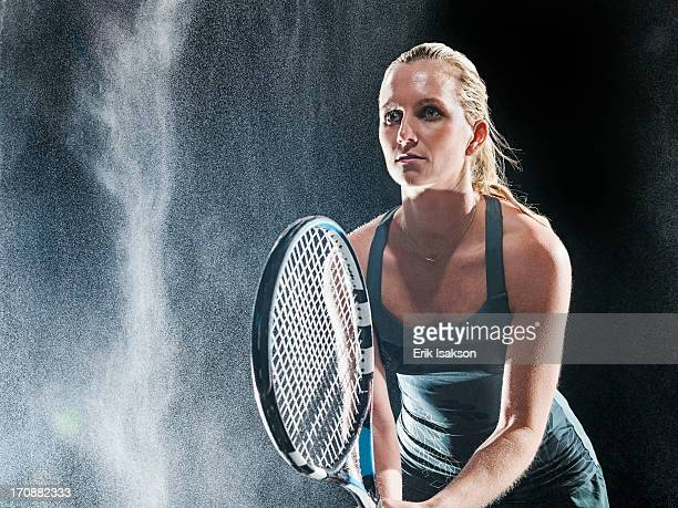 Caucasian tennis player standing in rain