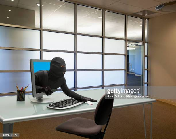 Caucasian thief coming out of computer monitor in office