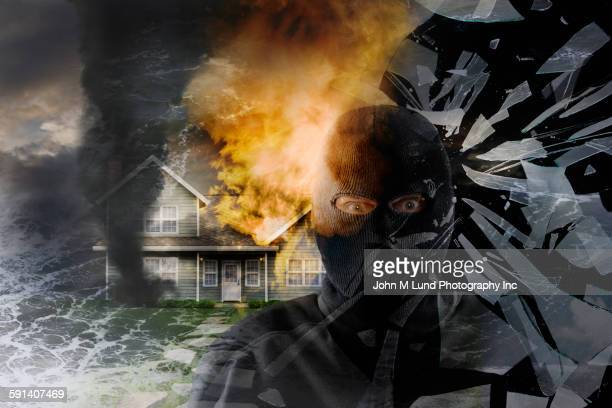 Caucasian thief shattering glass by burning house