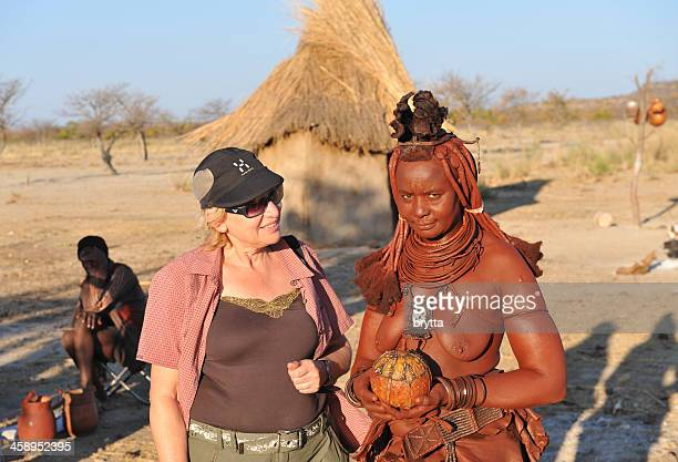 Caucasian tourist standing near Himba woman in Opuwo,Namibia