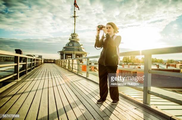 Caucasian tourist using camera on boardwalk