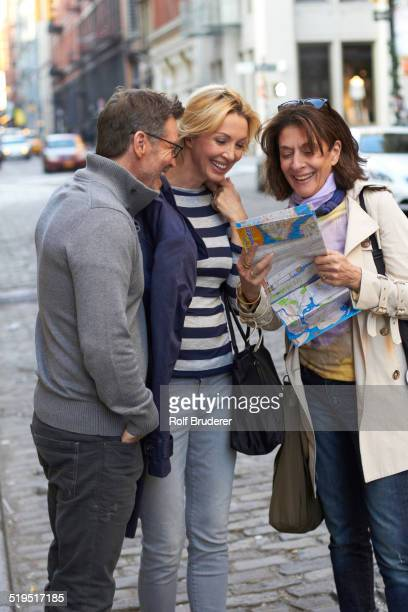 Caucasian tourists reading map on city street, New York City, New York, United States