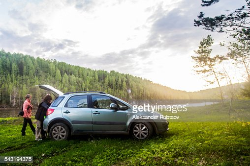 Caucasian tourists unloading car in remote landscape