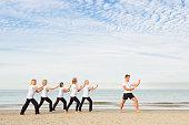 Caucasian trainer leading older women in tai chi on beach