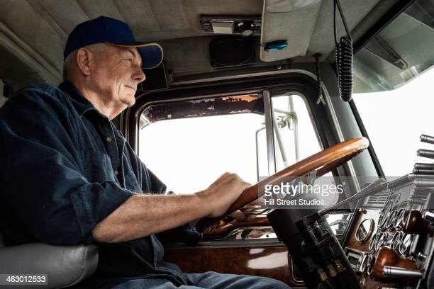 Caucasian trucker driving semi-truck