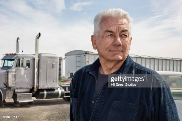 Caucasian trucker standing outside truck