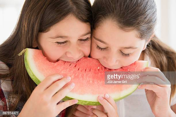 Caucasian twin sisters eating watermelon