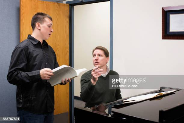Caucasian vocal teacher and student singing at piano