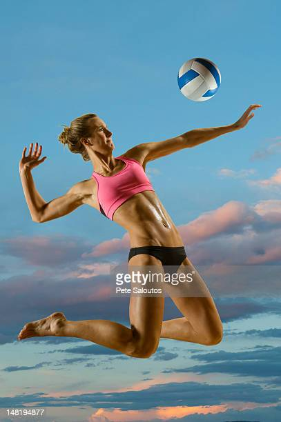 Caucasian volleyball player hitting volleyball