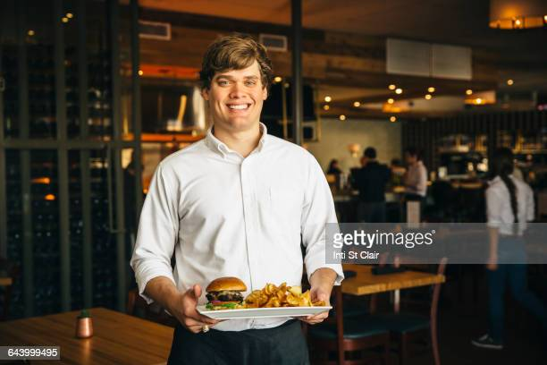 Caucasian waiter carrying cheeseburger and chips in cafe