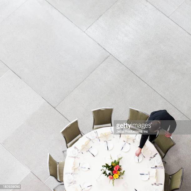 Caucasian waiter setting table in dining room