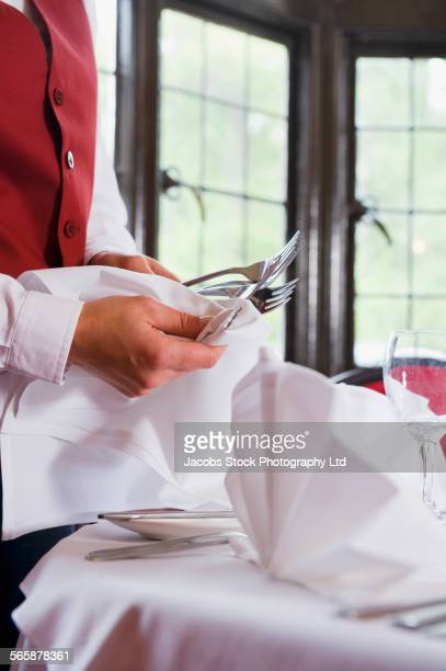Caucasian waiter setting table in restaurant