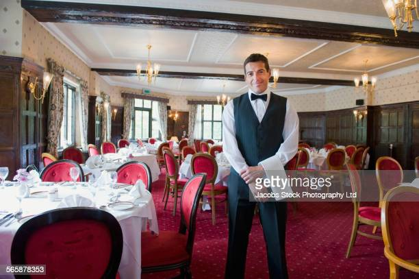 Caucasian waiter smiling in empty restaurant