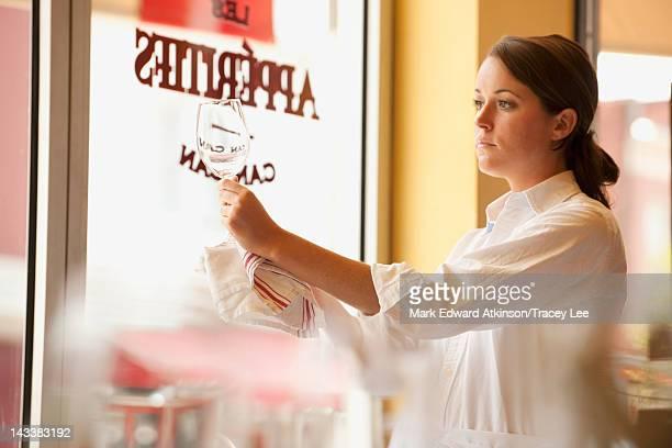 Caucasian waitress cleaning wine glass in restaurant