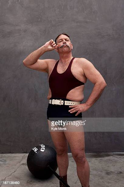 Caucasian weight lifter twirling his mustache
