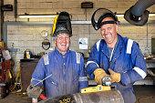 Caucasian welders smiling in workshop