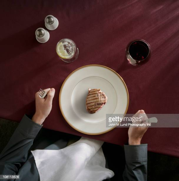Caucasian woman about to eat portion of meat