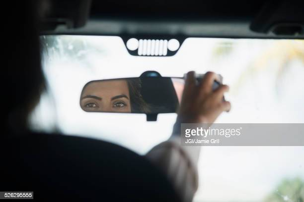 Caucasian woman adjusting rear view mirror in car