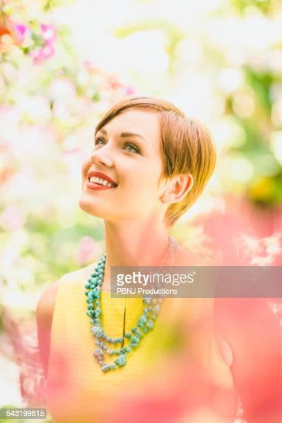 Caucasian woman admiring flowers in garden