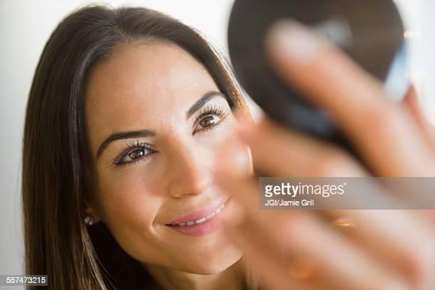 Caucasian woman admiring herself in compact mirror