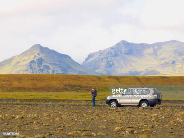 Caucasian woman admiring mountains from remote road, Vik, Southland, Iceland