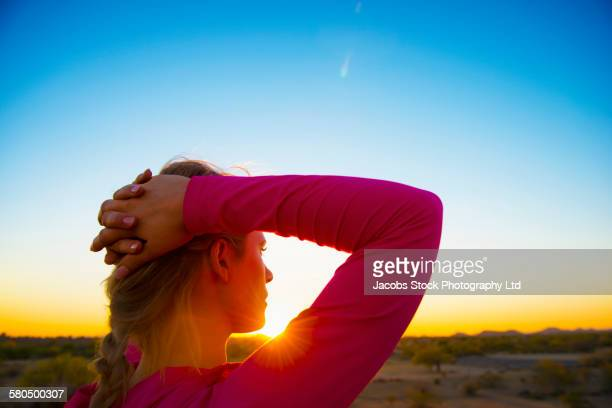 Caucasian woman admiring remote field under sunset set