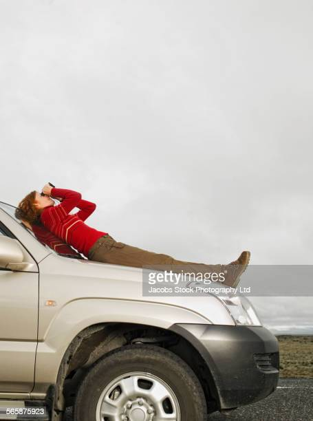 Caucasian woman admiring sky with binoculars on car