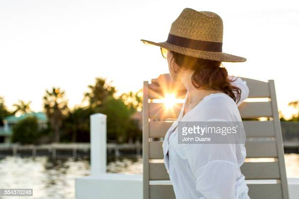 Caucasian woman admiring sunset from deck chair