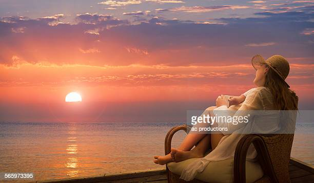 Caucasian woman admiring sunset on beach