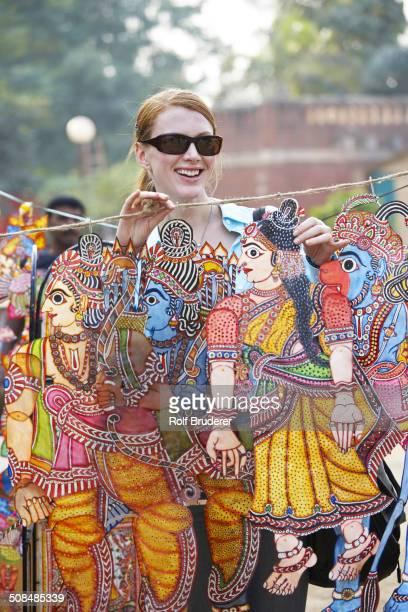 Caucasian woman admiring traditional art in outdoor market