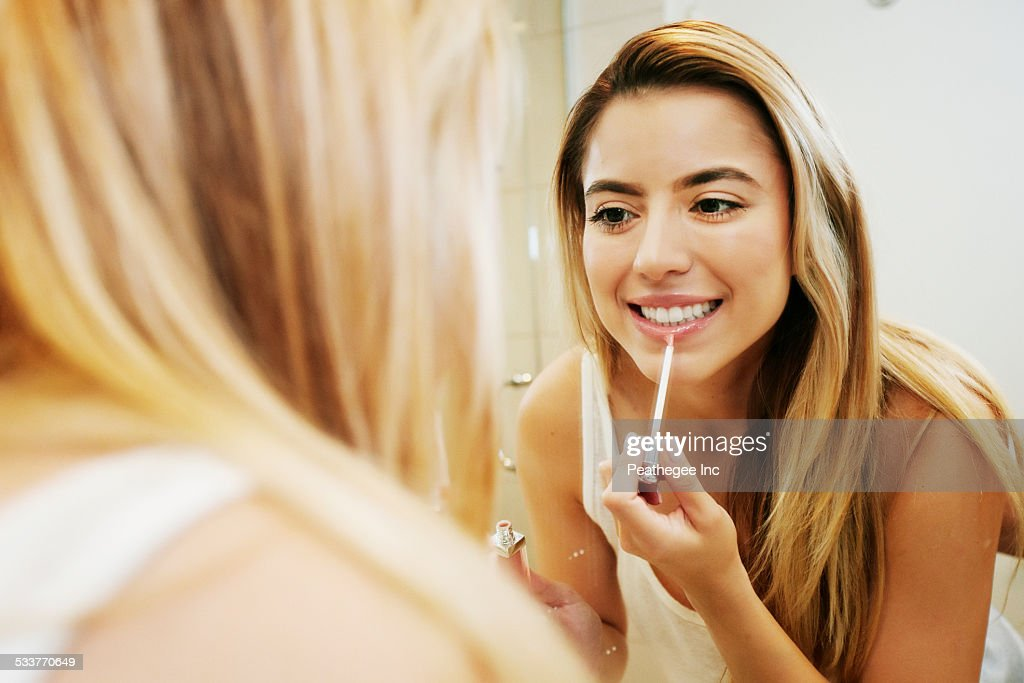 Caucasian woman applying makeup in bathroom mirror