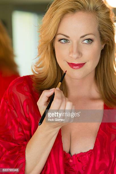 Caucasian woman applying makeup