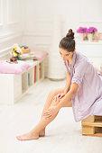 Caucasian woman applying moisturizer to leg