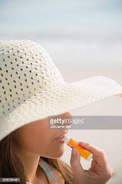 Caucasian woman applying sunscreen lip balm at beach