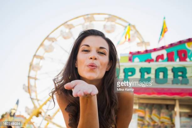 Caucasian woman at carnival blowing a kiss