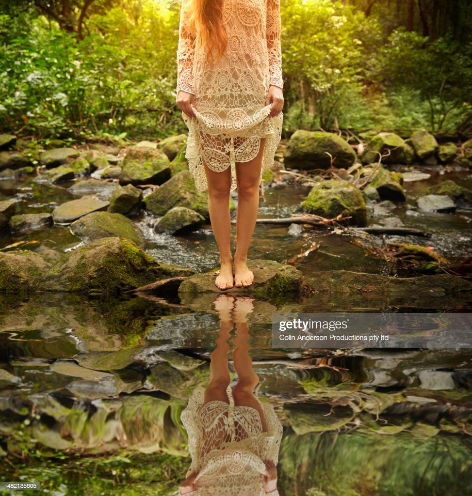 Caucasian woman at creek in woods