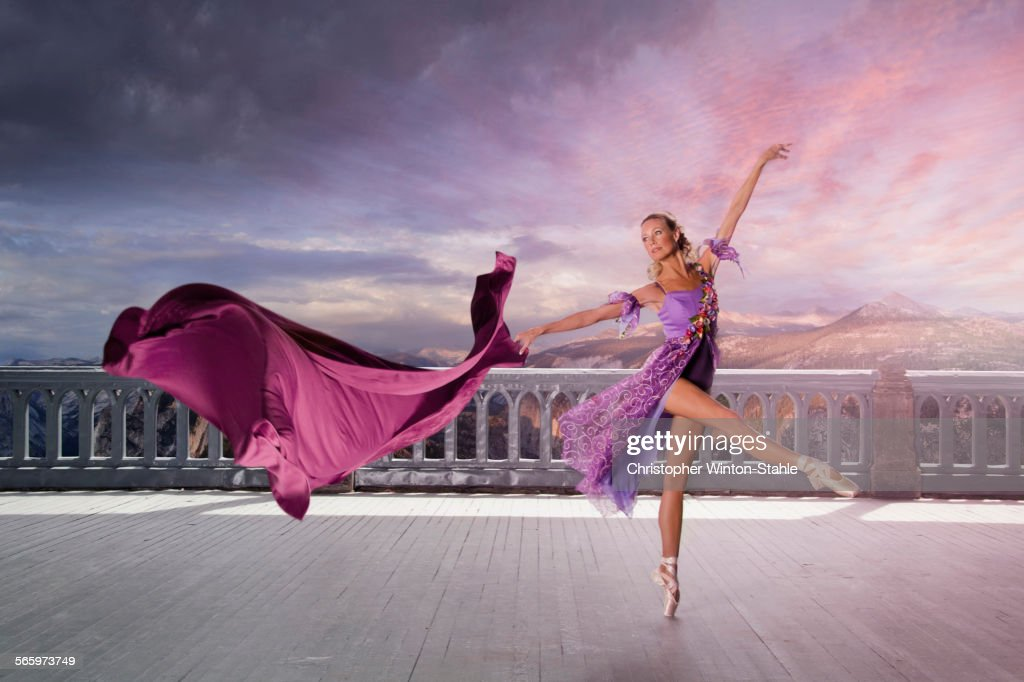 Caucasian woman ballet dancing on balcony