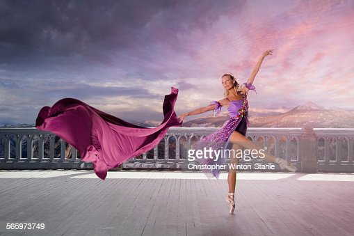 Caucasian woman ballet dancing on balcony