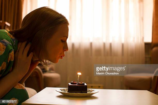Caucasian woman blowing birthday candle on cupcake