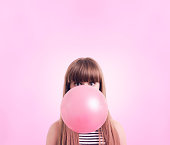 Caucasian woman blowing large bubble gum bubble