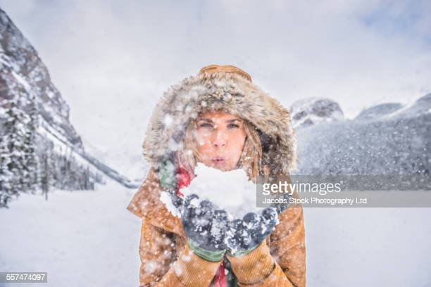 Caucasian woman blowing snow near mountains, Lake Louise, Alberta, Canada