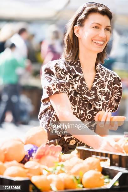 Caucasian woman buying eggs at market