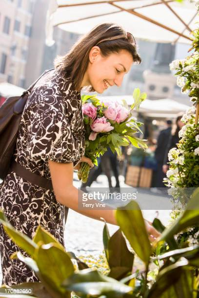 Caucasian woman buying flowers at market