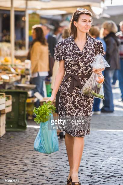 Caucasian woman buying produce at market