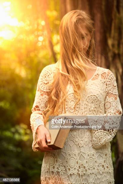 Caucasian woman carrying book in woods