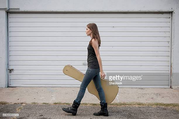 Caucasian woman carrying guitar case on sidewalk